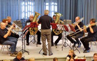 Sieben Blechbläser mit Dirigent spielen auf einer Bühne