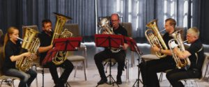 Eine Tubistin, ein Tubist, und 3 Euphonisten spielen in halb-Kreis
