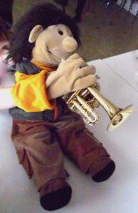 Eine Puppe spielt auf einer Piccolo-Trompete